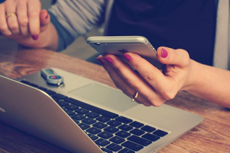 Laptop steht auf Tisch, eine Frau sitzt davor und hält Smartphone in der Hand