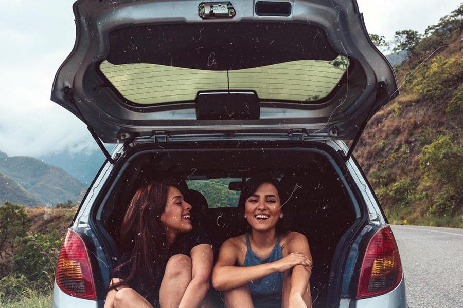 zwei junge Frauen sitzen lachend im aufgeklappten Kofferraum eines Autos