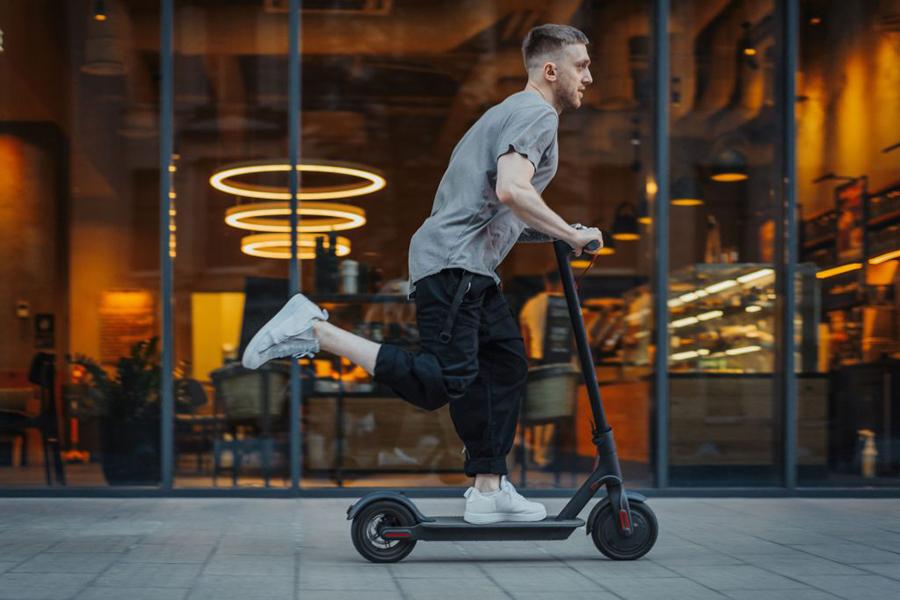 Junger Mann fährt auf E-Scooter an Geschäft vorbei