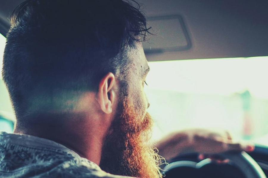 Mann mit Bart sitzt hinterm Steuer und schaut nach vorne