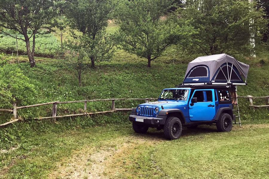 Blauer Geländewagen mit Dachzelt fährt über ländliche Straße