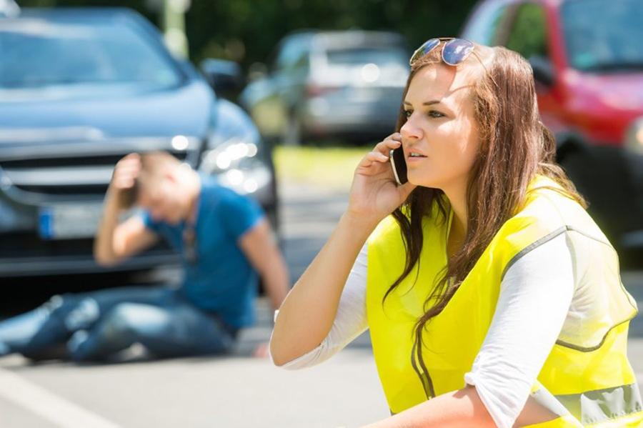 Frau in Warnweste am Handy, im Hintergrund sitzt ein Mann am Boden und hält sich den Kopf