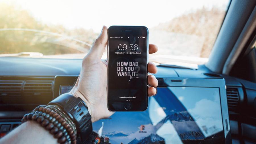 Hand die ein Smartphone in die Kamera hält, Person sitzt im Auto