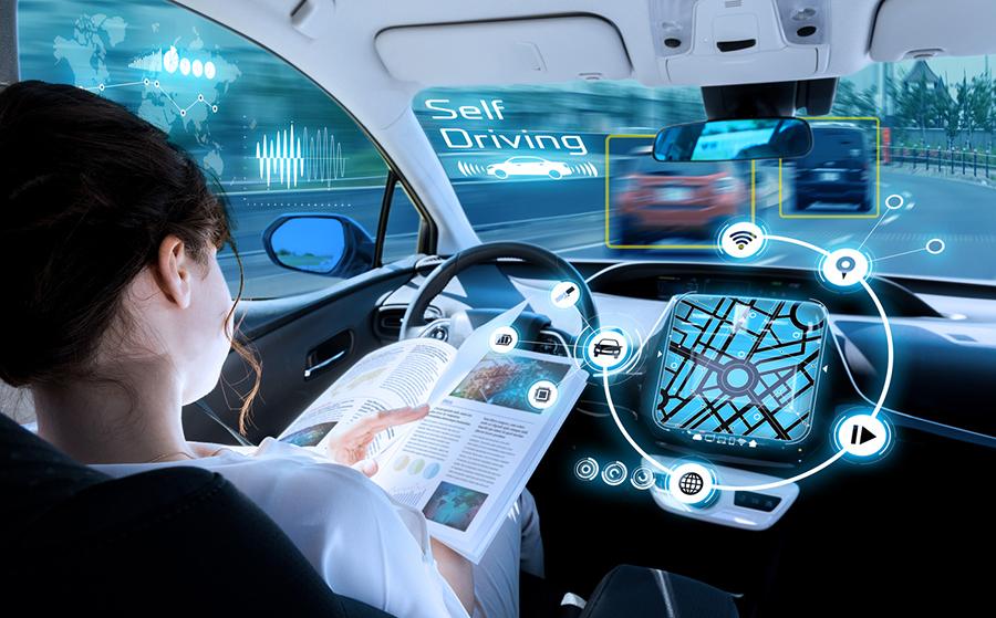 Frau sitzt im Auto hinterm Steuer und liest während sich das Auto autonom um die Technik zu kümmern scheint