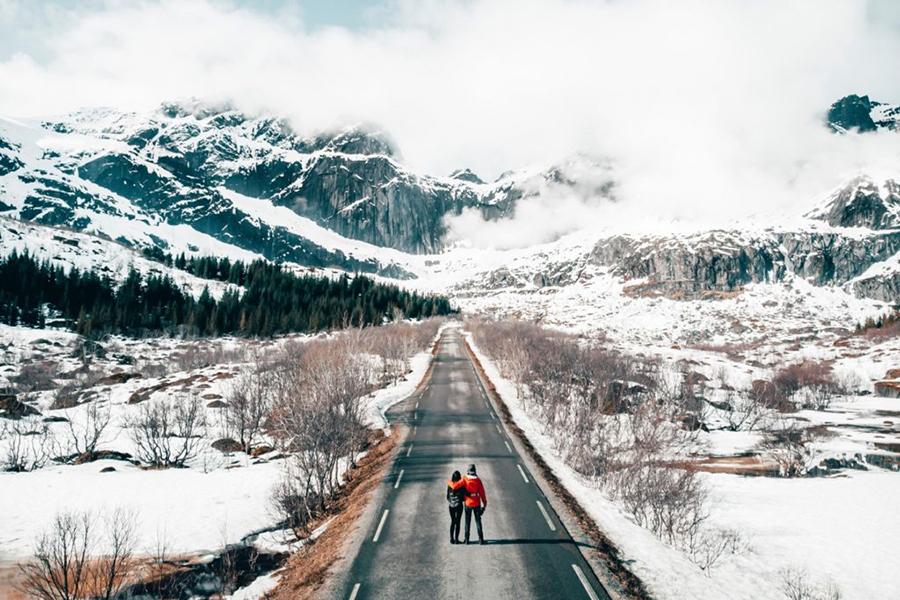 Zwei Menschen stehen auf unbefahrener Straße umgeben von einer Winterlandschaft