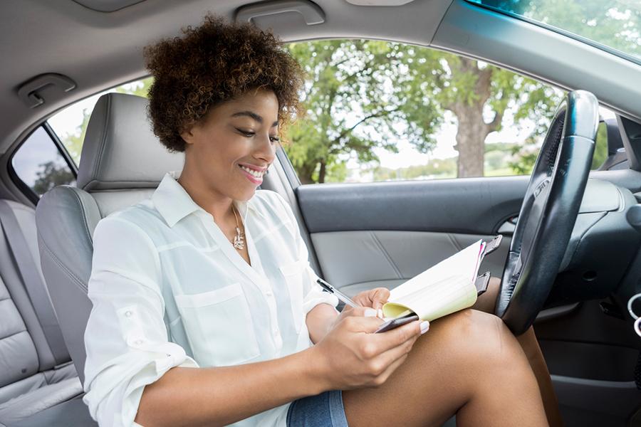 Junge Frau sitzt lächelnd im Auto und macht Notizen in einem Heft