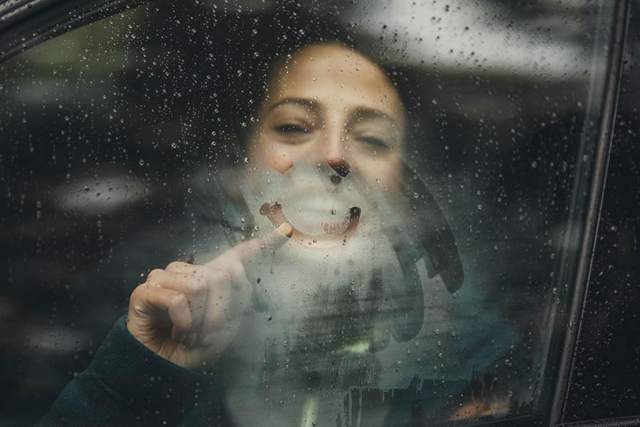 Frau sitzt im Auto und malt mit dem Finger auf beschlagene Scheibe