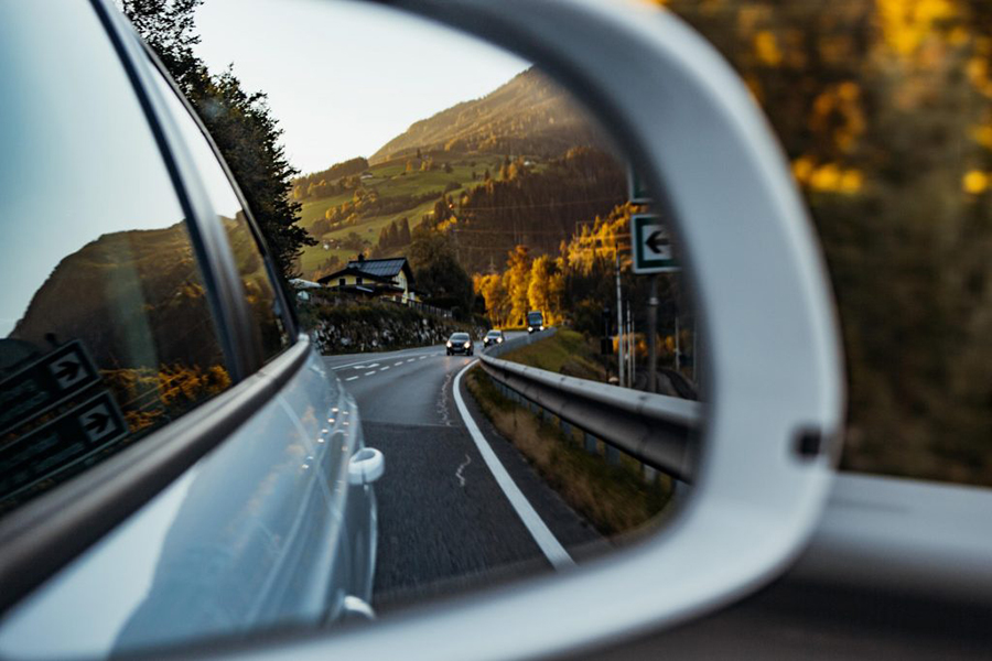 rearview mirror of car shows road that lies behind