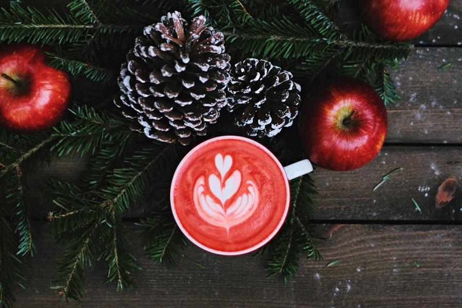 Tannenzweige, Äpfel, ein Heißgetränk und Tannenzapfen