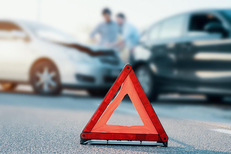 Warndreieck steht auf der Straße, im Hintergrund verschwommen ein Autounfall