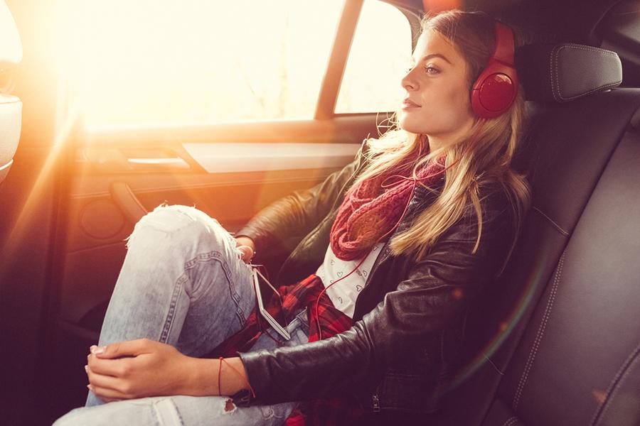 Frau sitzt entspannt auf Rücksitz eines Autos und trägt rote Kopfhörer