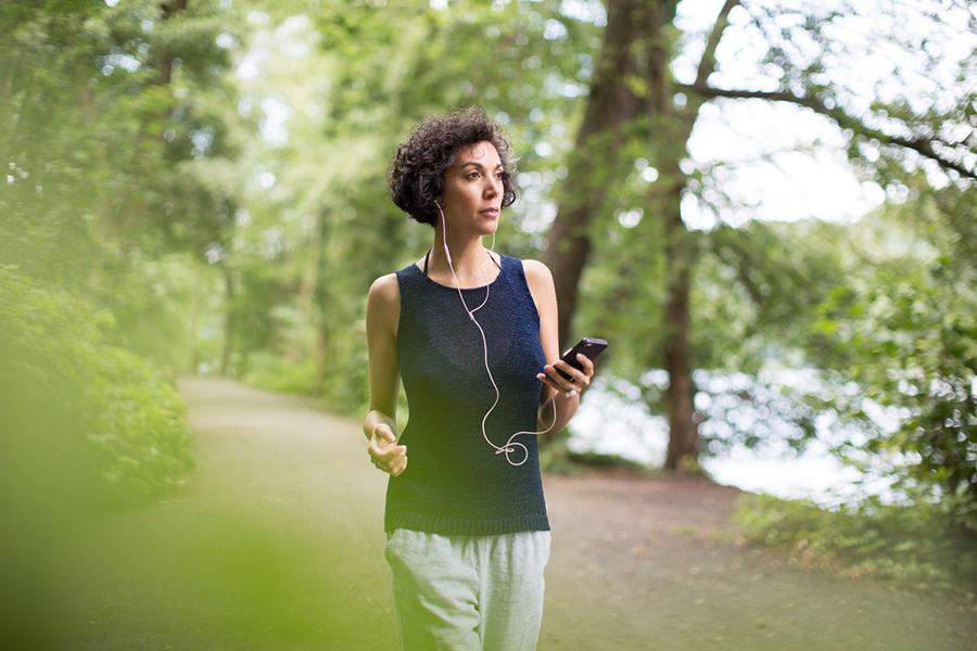 Frau joggt mit Handy in der Hand und Kopfhörern durch Park