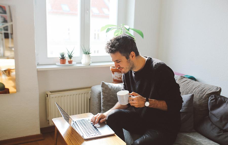 Mann sitzt auf Sofa, mit Tasse in der Hand und arbeitet im Homeoffice an Laptop, der auf Couchtisch steht