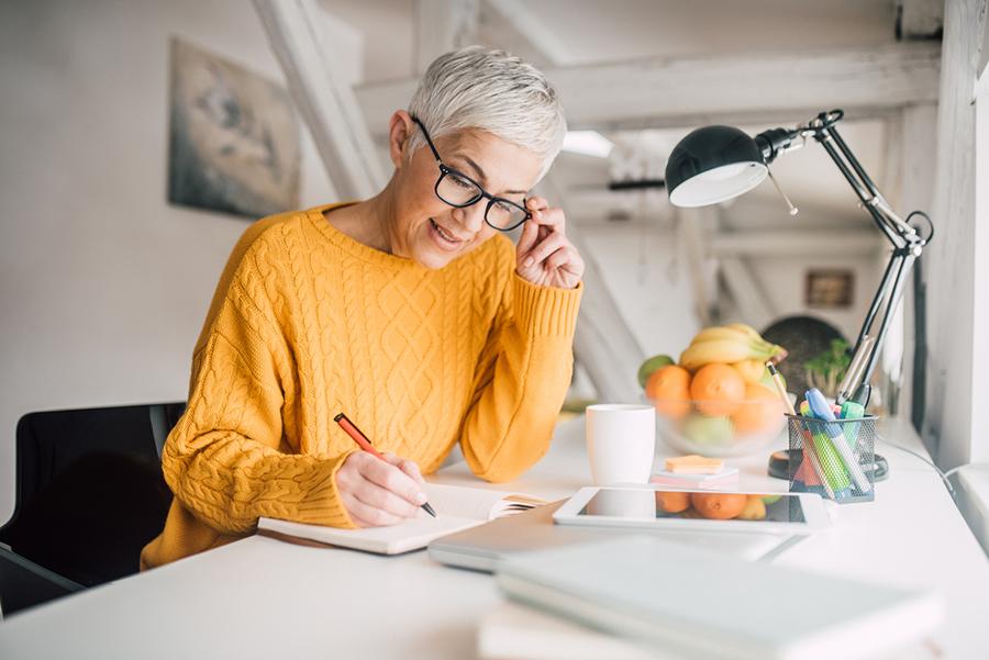Frau mit grauen Haare und Brille arbeitet an ihrem Schreibtisch