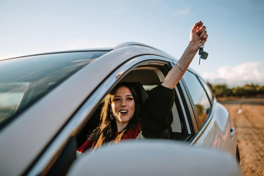 Frau sitzt am Steuer eines Autos und streckt den Arm begeistert aus dem Fenster