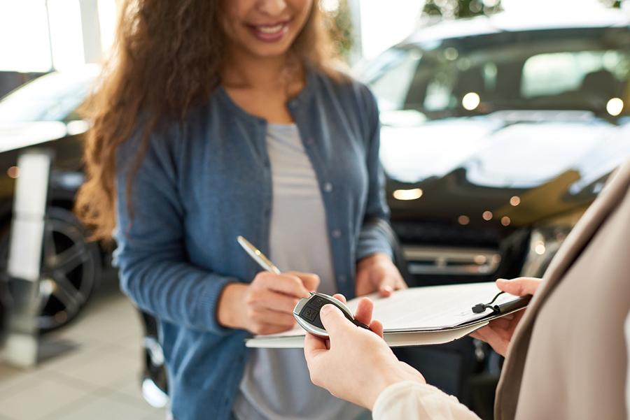Frau unterzeichnet auf einem Klemmbrett, andere Person hat Autoschlüssel in der Hand, Autos im Hintergrund zu sehen