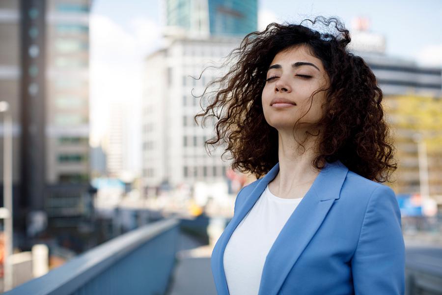 Frau im blauen Blazer hält mit geschlossenen Augen ihr Gesicht ins Wind, Straßenkulisse im Hintergrund