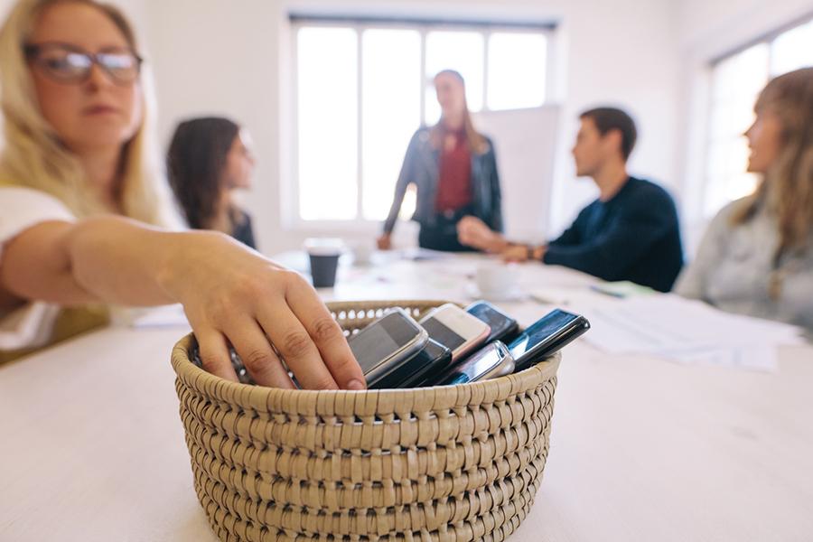 Menschen an Konferenztisch, im Vordergrund ein Korb, in dem Smartphones gesammelt werden