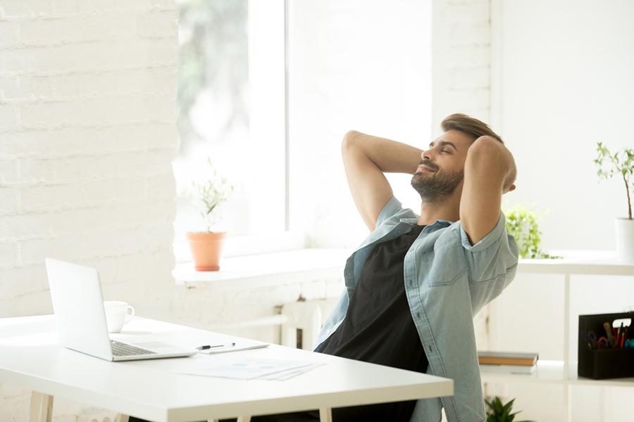 Mann sitzt am Schreibtisch und legt entspannt die Hände in den Nacken und lehnt sich zurück