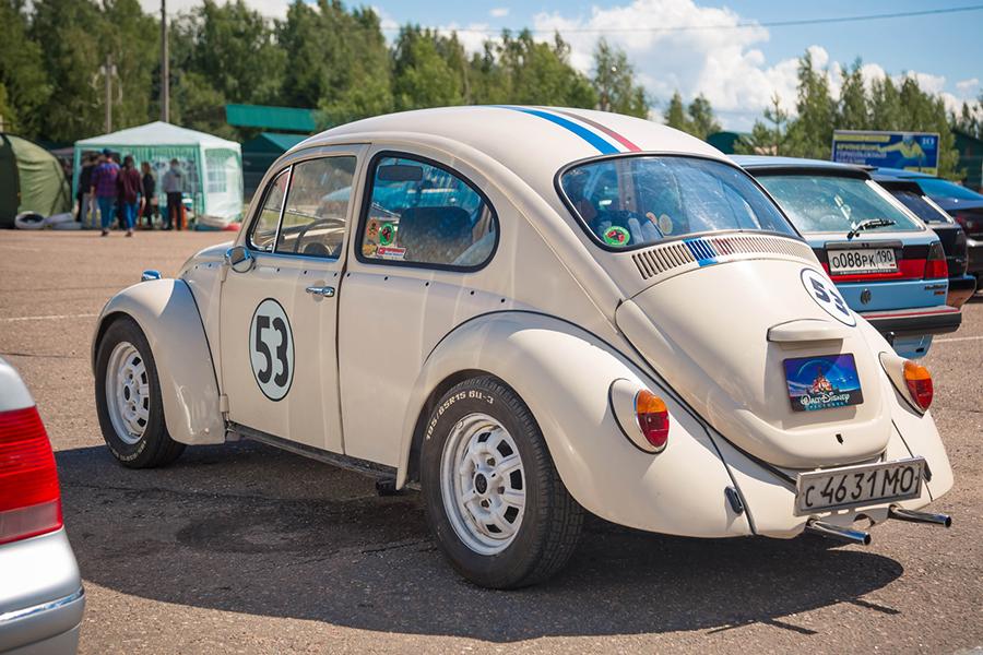VW Käfer Herbie seitlich von hinten auf einem Parkplatz