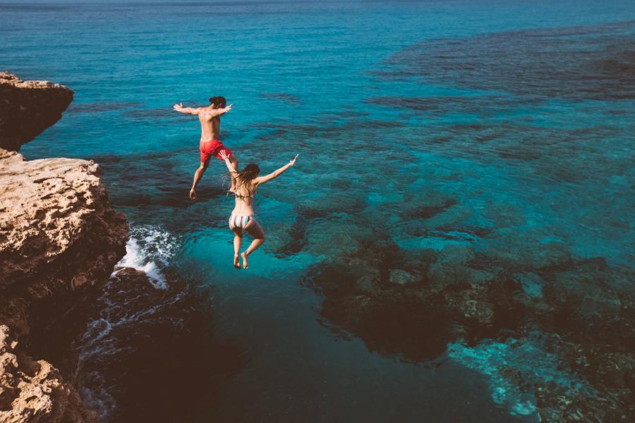 Mann und Frau spring von einer Klippe ins Meer