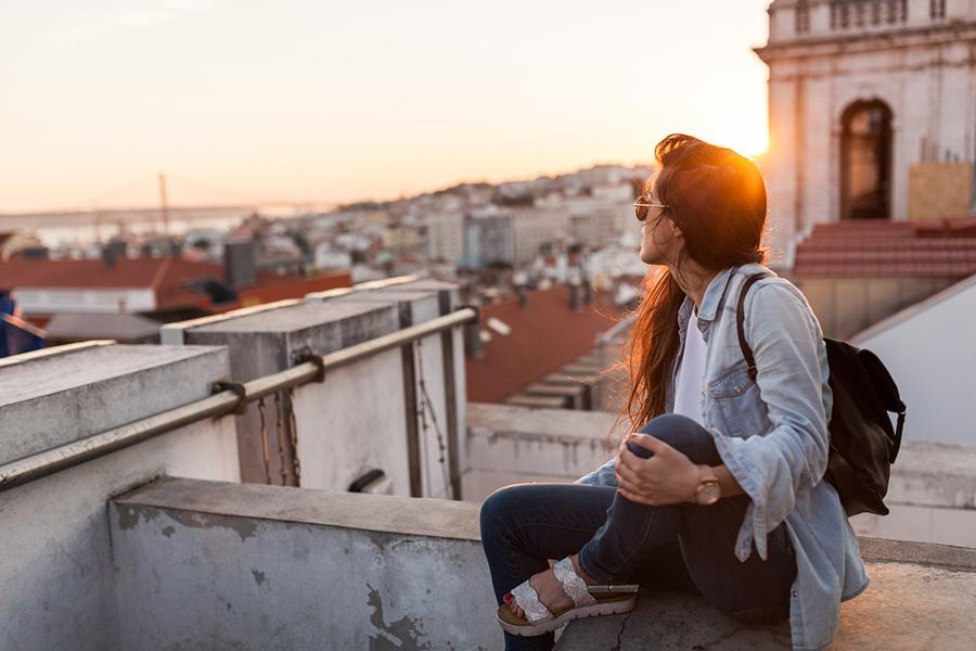 Frau sitzt auf Dach eines Gebäudes und schaut bei Sonnenuntergang über die Dächer
