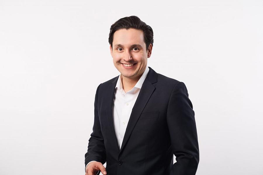 Lächelnder Mann im Anzug vor weißem Hintergrund