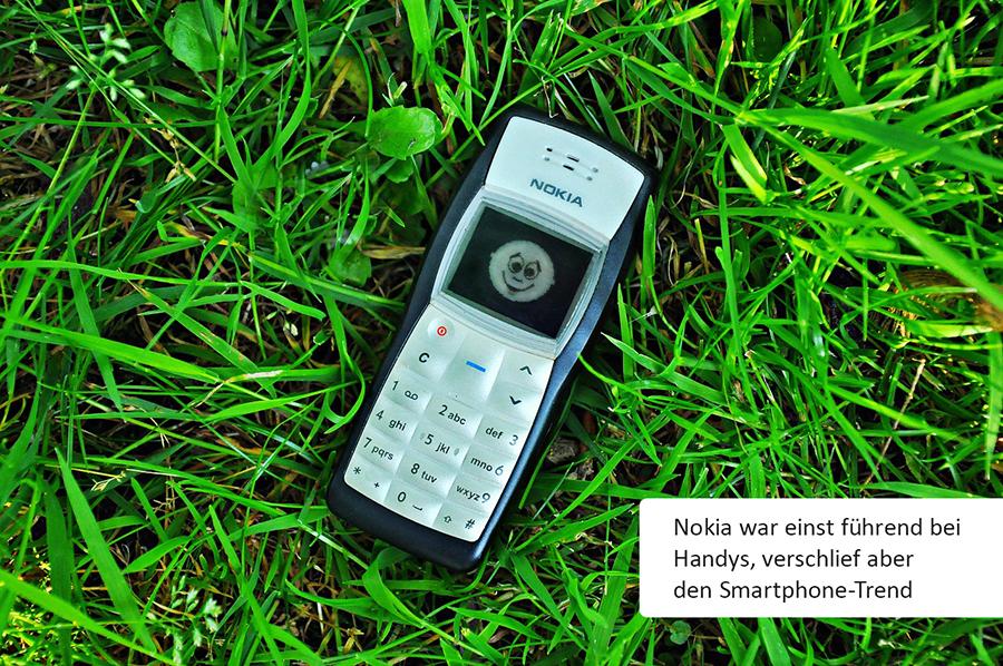 """Nokia-Handy liegt im Gras, in einer Box steht """"Nokia war einst führend bei Handys, verschlief aber den Smartphone-Trend"""""""