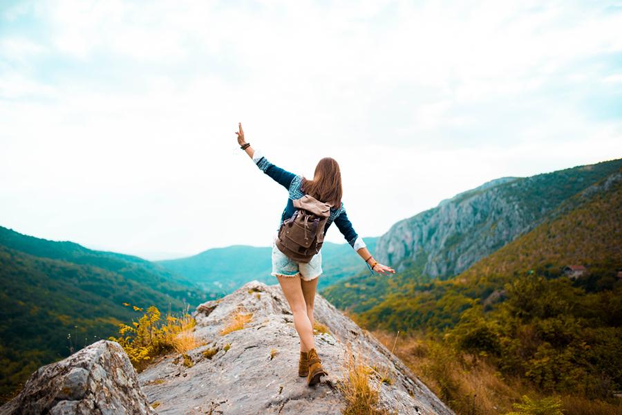Frau balanciert auf Berg in Berglandschaft