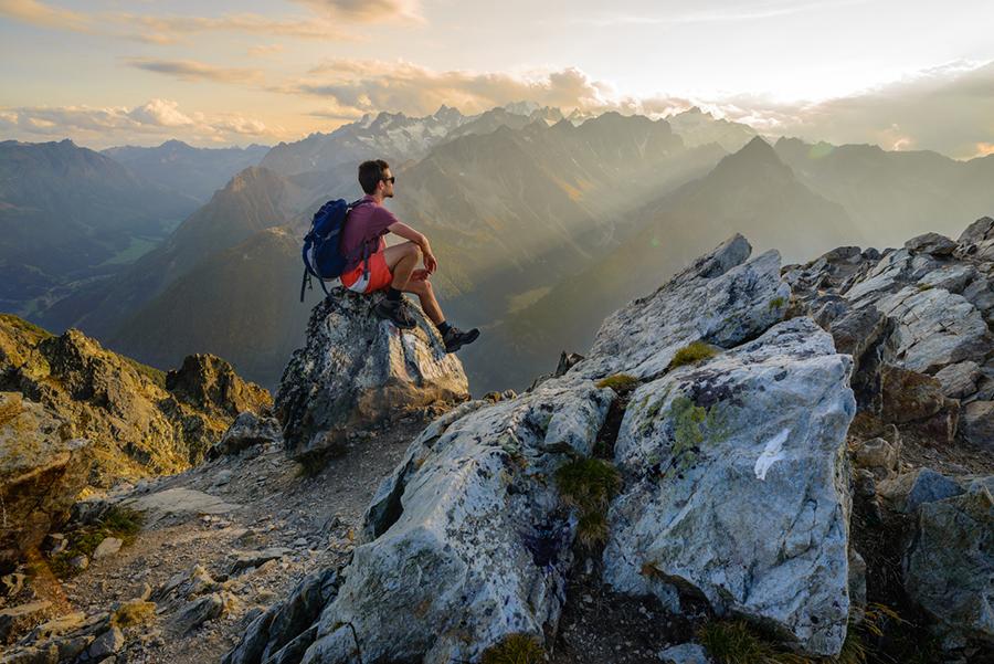 Mann sitzt auf Berg und genießt die Aussicht