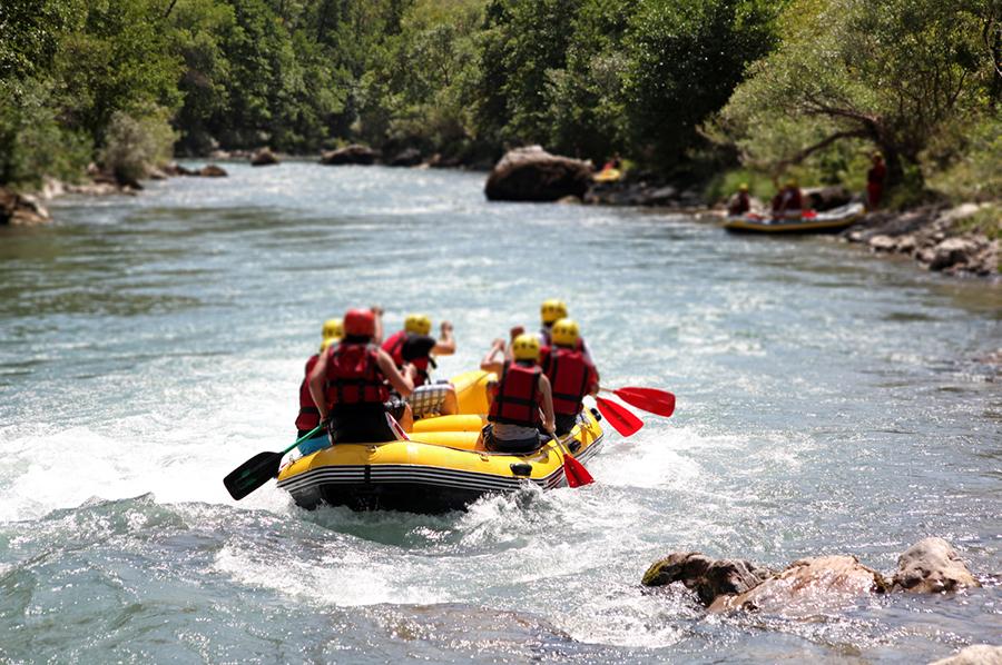 Sechs Personen paddeln in Raftingboot auf einem Fluss