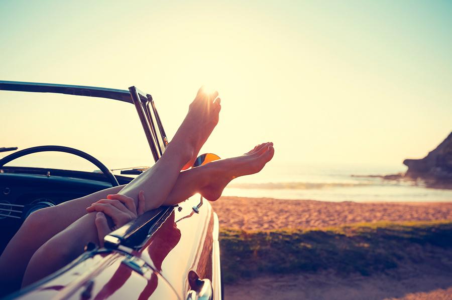 Offenes Cabrio geparkt am Strand, Füße einer Frau baumeln aus Auto