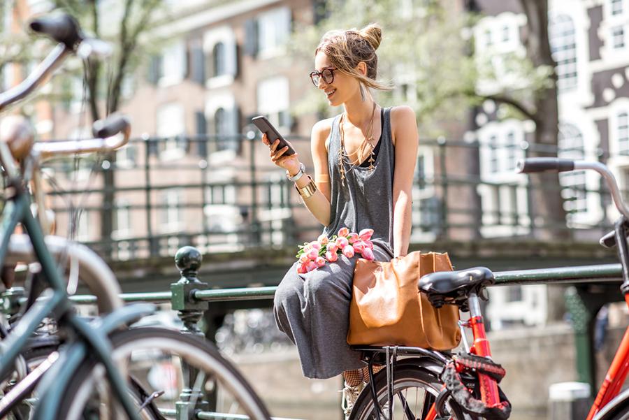 Frau in Amsterdam sitzt auf Geländer schaut aufs Smartphone