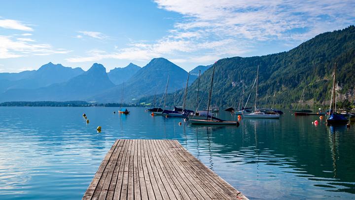Steg der in einen klaren See ragt, Aussicht auf Berge