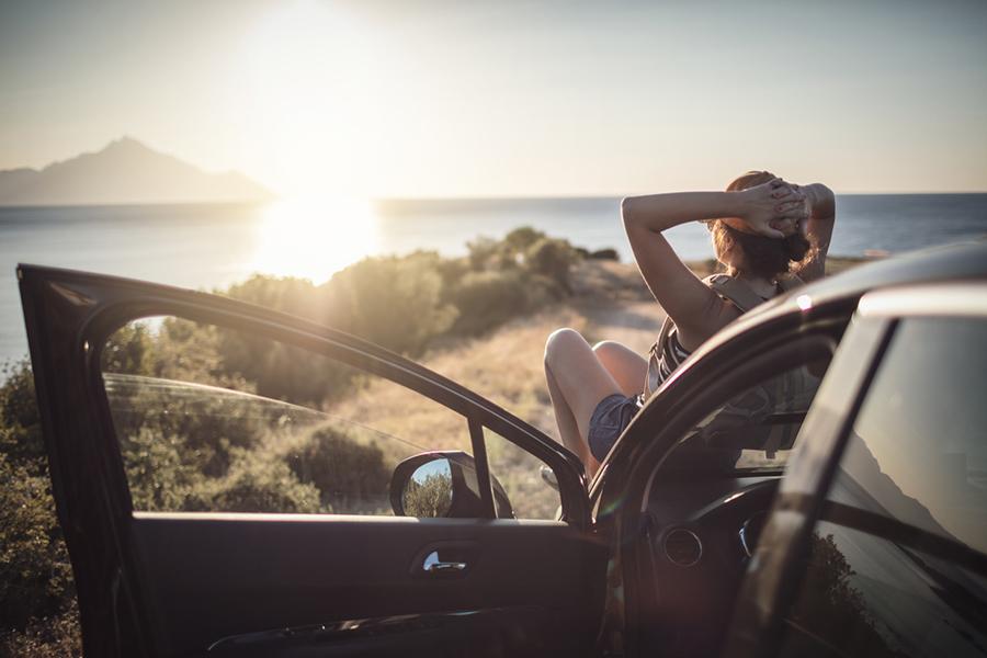 Frau entspannt während Roadtrip am Meer auf Motorhaube ihres Autos
