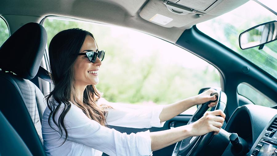 Junge Frau mit Sonnenbrille sitzt gut gelaunt im Auto hinterm Steuer