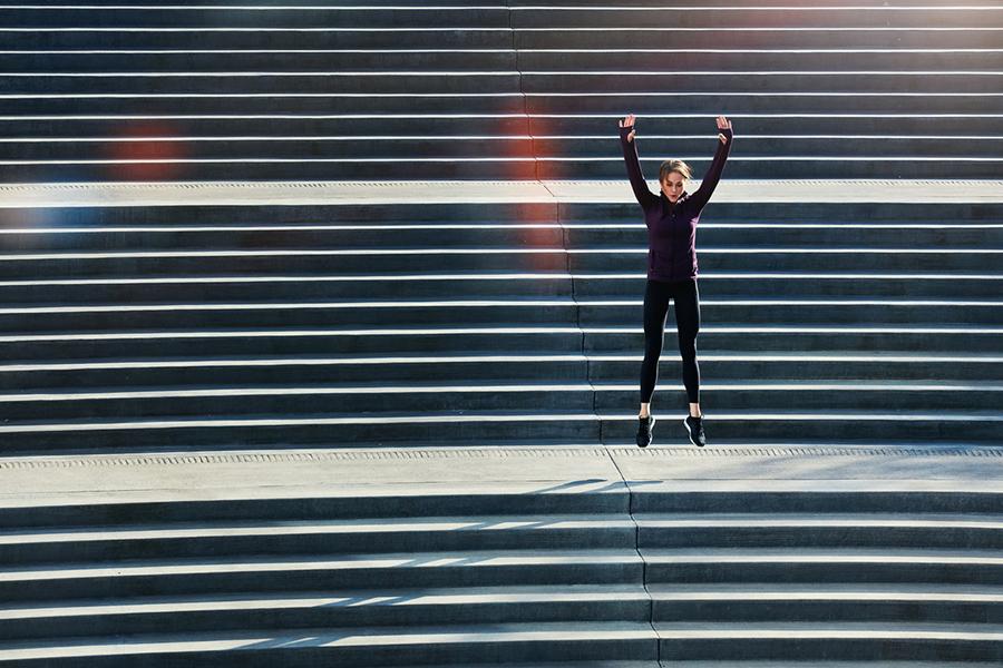 Frau in Sportkleidung macht Hampelmänner auf einer Treppe