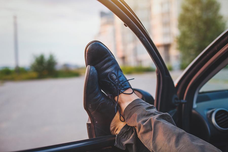 Überschlage Beine, die im geöffneten Autofenster liegen