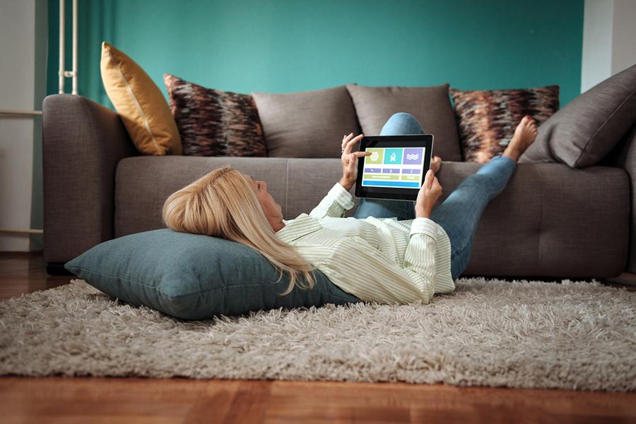 Frau liegt auf dem Boden, Füße liegen auf dem Sofa, sie schaut auf ein Tablet