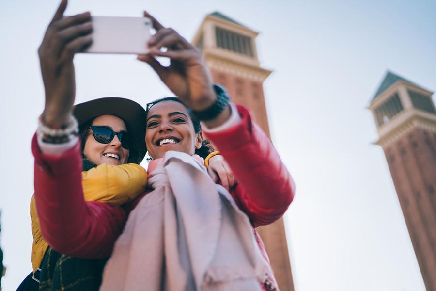 Zwei Frauen machen ein gemeinsames Selfie vor Sehenswürdigkeit