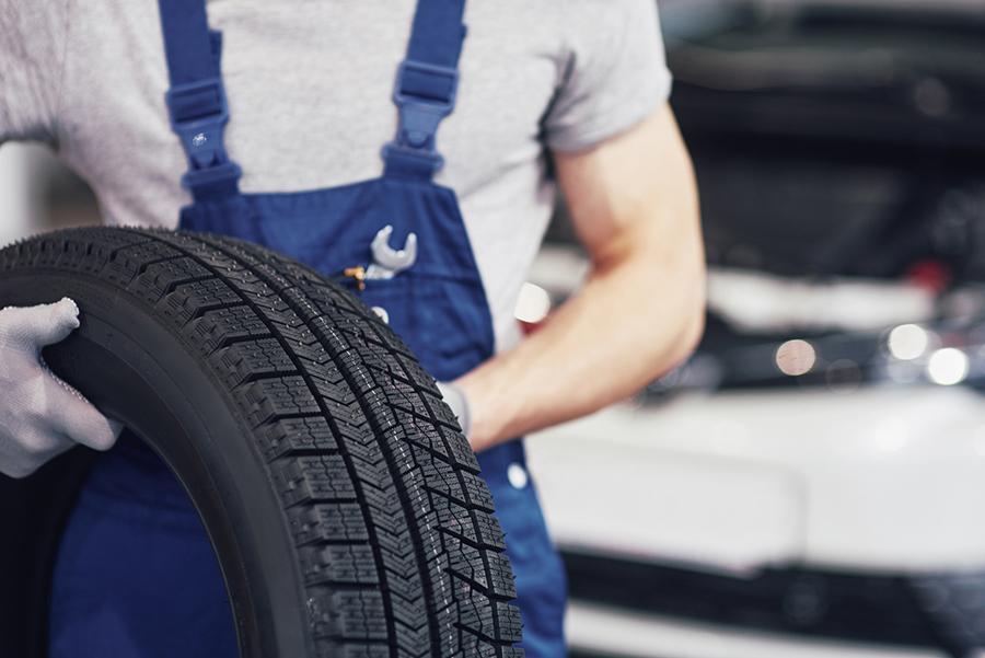 Mechaniker hält Winterreifen für Reifenwechsel