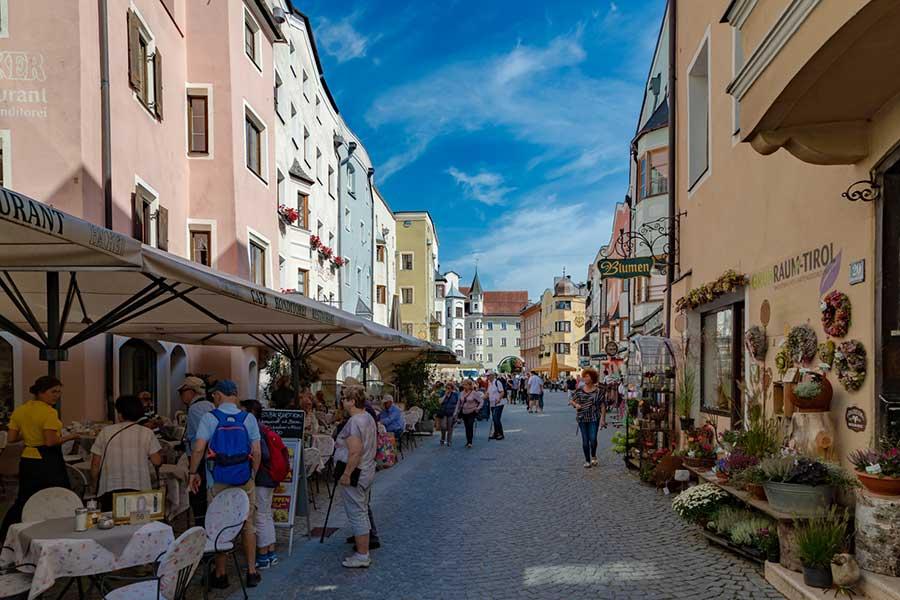 Blick auf belebte Straße in einer Altstadt, die von Restaraunts und einem Blumenladen gesäumt ist