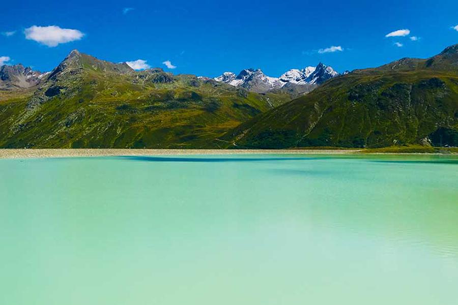 Blick auf einen klaren hellblauen See bei schönstem Wetter