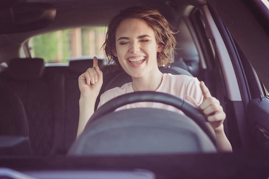 Frau sitzt im Auto hinterm Steuer und tanz gut gelaunt