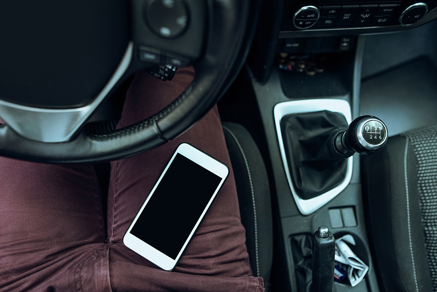 Smartphone liegt auf rechtem Bein eines Autofahrers