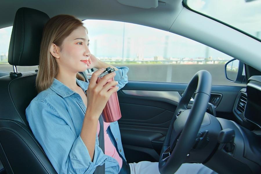 Frau mit Becher in der Hand am Steuer eines selbstfahrendes Autos
