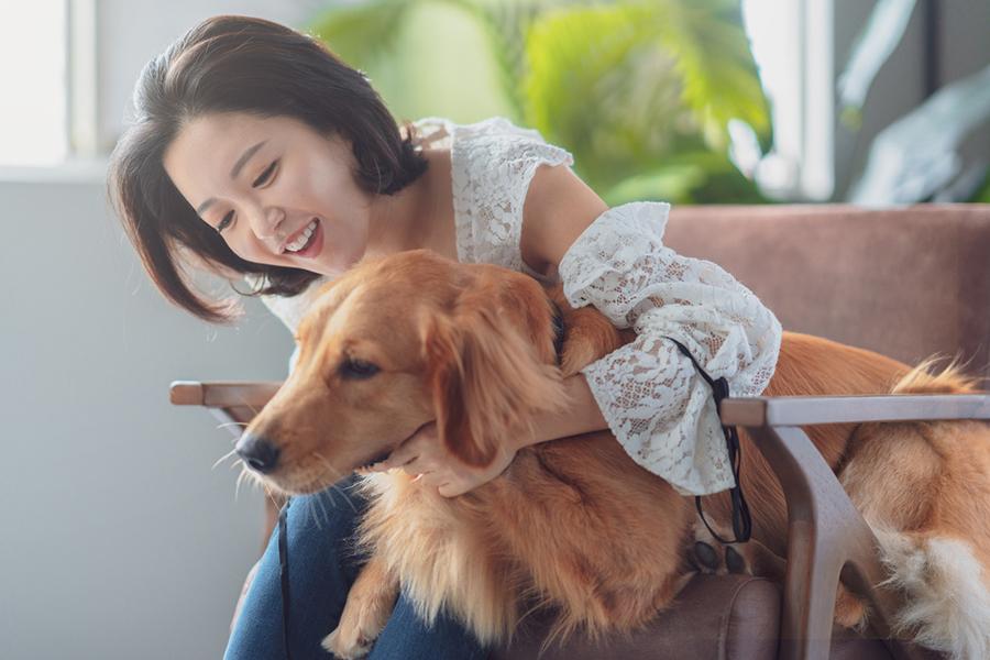 Junge Frau streichelt ihren Hund und lacht