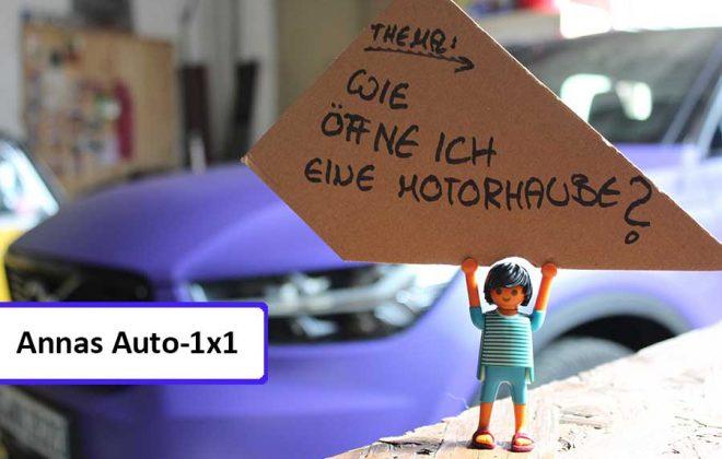"""Playmobilmännchen hält Schild hoch mit Aufschrift """"Wie öffne ich eine Motorhaube?"""""""