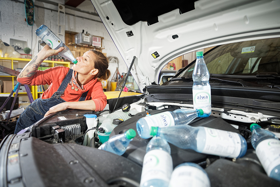 Geöffnete Motorhaube in der leere Wasserflaschen liegen, Mechanikerin trinkt aus Wasserflasche