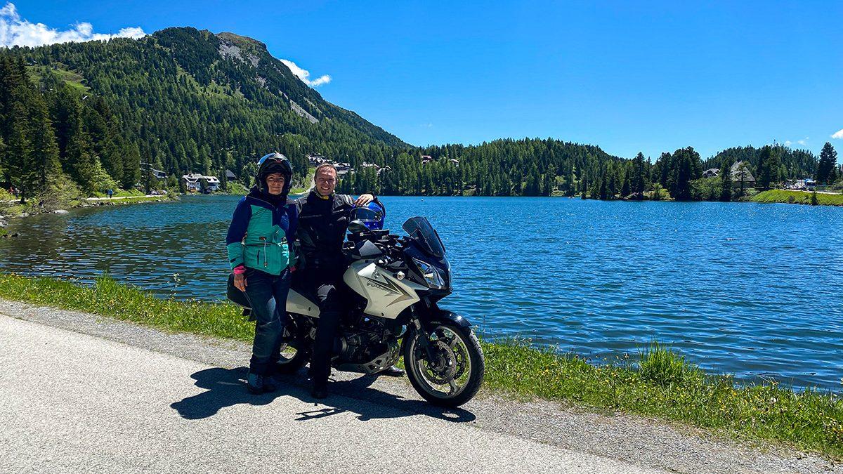 Pärchen auf Motorrad vor See und Berg im Hintergrund